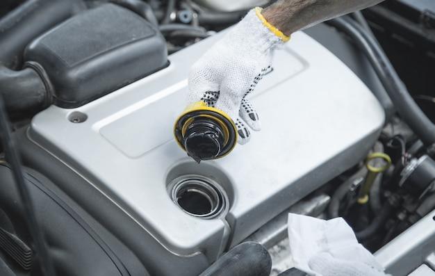 Mecânico de automóveis verifica o óleo do sistema do motor do carro.