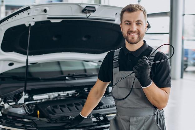 Mecânico de automóveis verificando um carro em uma oficina de automóveis