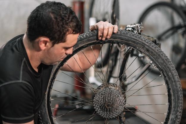Mecânico de bicicletas em uma oficina no processo de reparo.