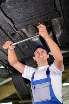 Mecânico de carro que examina a suspensão do carro do automóvel levantado.