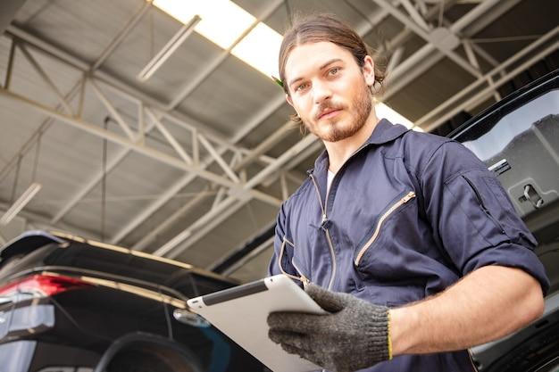 Mecânico de homem bonito de uniforme está trabalhando no serviço automotivo com veículo elevado e tablet.