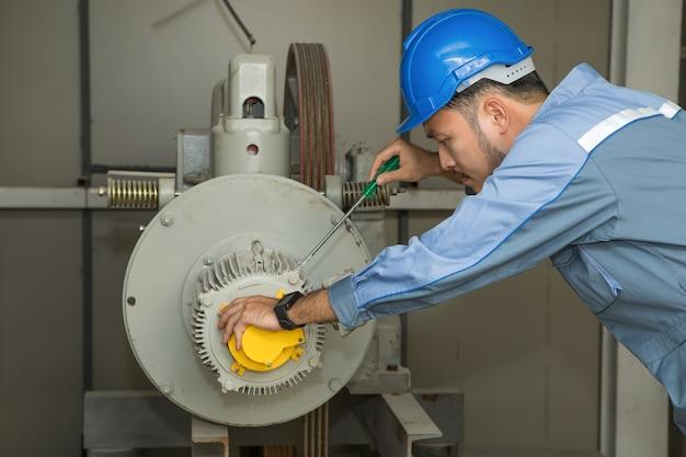 Mecânico de manutenção que repara o elevador motor para elevadores