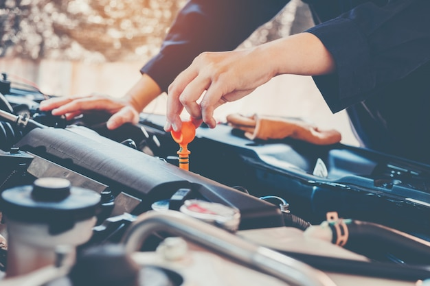 Mecânico de óleo de motor de carro trabalhando no serviço de reparação automóvel