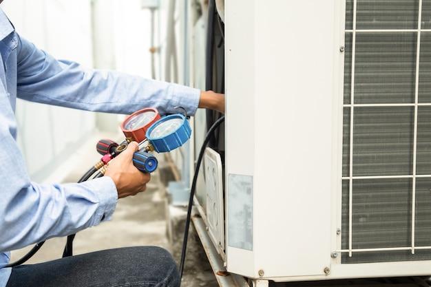 Mecânico de reparo de ar usando equipamento de medição para encher condicionadores de ar de fábrica industrial e verificação de unidade de compressor de ar externo de manutenção.