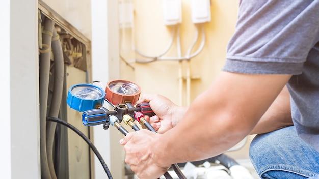 Mecânico de reparo de ar usando equipamento de medição para encher condicionadores de ar de fábrica industrial