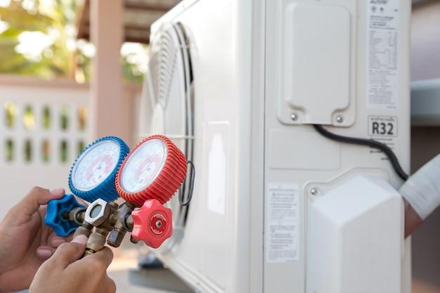 Mecânico de reparo de ar usando equipamento de medidor de pressão para encher o ar condicionado doméstico após a limpeza