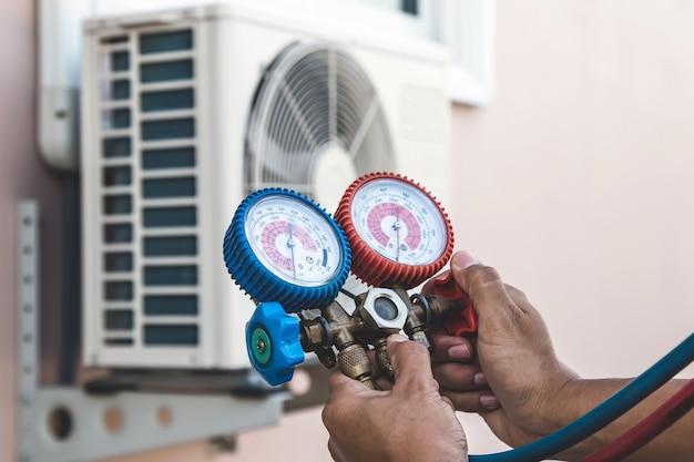 Mecânico de reparo de ar usando equipamento medidor de pressão para encher ar condicionado doméstico.