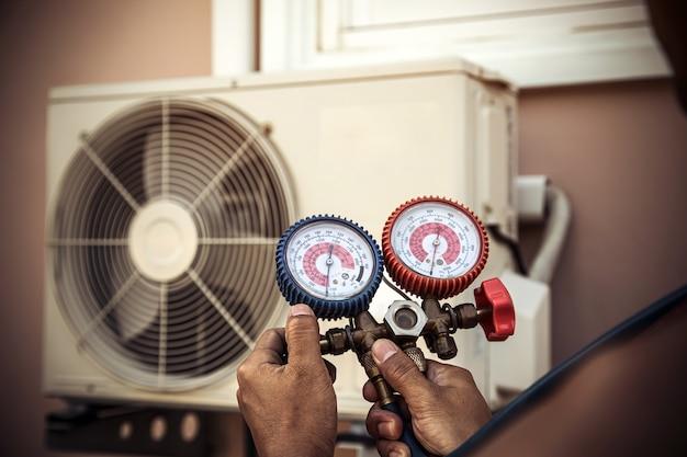 Mecânico de reparo de ar usando equipamento medidor de pressão para encher o ar condicionado doméstico.