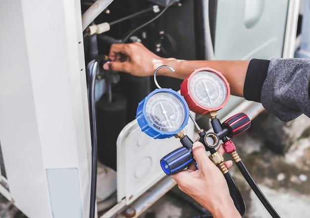 Mecânico de reparo de ar utilizando equipamento de medição para enchimento de condicionadores de ar de fábricas industriais.