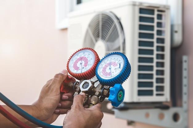 Mecânico de reparo do ar usando equipamento de manômetro para encher o ar condicionado doméstico.