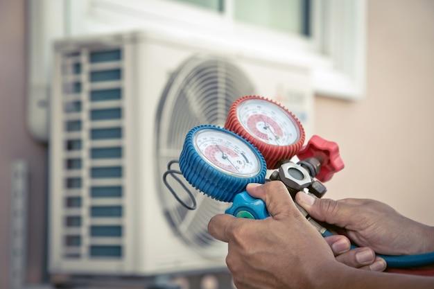 Mecânico de reparo do ar usando equipamento de manômetro para encher o ar condicionado doméstico