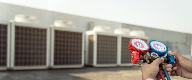 Mecânico de reparo do ar usando equipamento de medição para encher condicionadores de ar de fábricas industriais