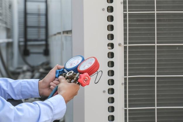 Mecânico de reparo do ar usando equipamento de medição para encher condicionadores de ar industriais de fábricas.