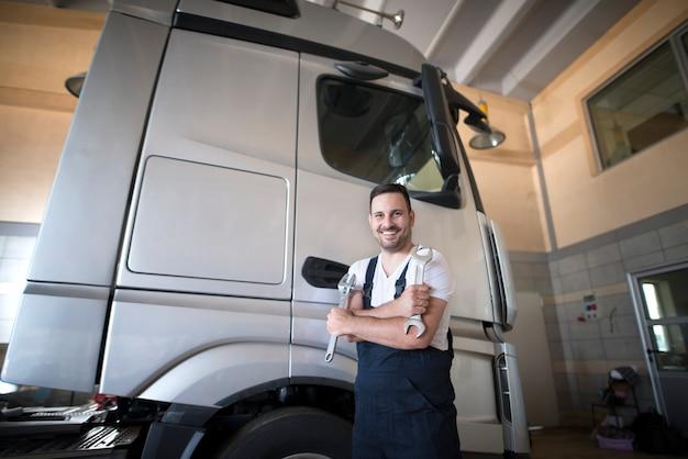 Mecânico de veículos profissional parado na oficina com os braços cruzados e uma chave inglesa pronta para começar a consertar o caminhão