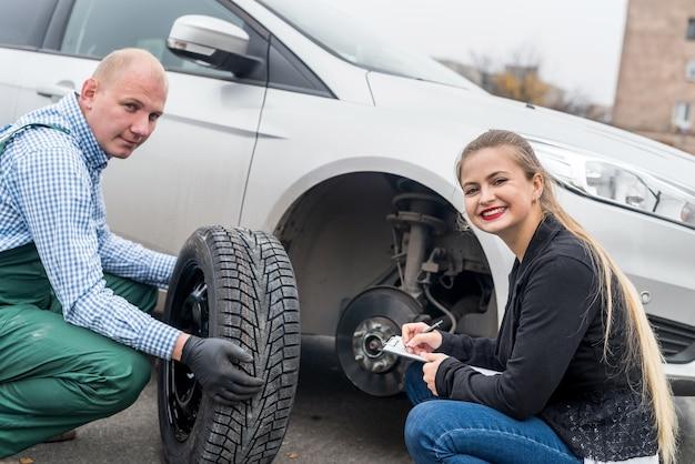 Mecânico e motorista olhando para a roda sobressalente Foto Premium