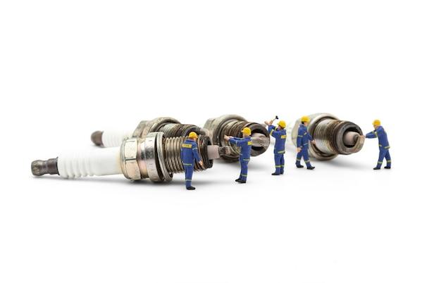 Mecânico em miniatura com velas de ignição de motor usadas velhas em fundo branco.
