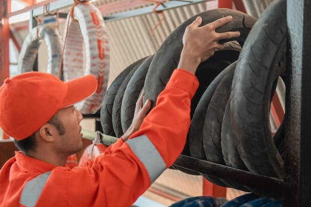 Mecânico em um uniforme de wearpack pega um pneu do rack em uma oficina de peças sobressalentes de motocicletas
