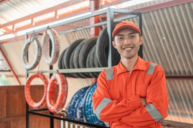 Mecânico em um wearpack vermelho com as mãos cruzadas enquanto na oficina com um suporte para pneus atrás