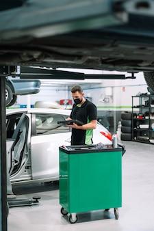 Mecânico em uma oficina verifica a eletrônica da atualização do software do carro com uma computação moderna