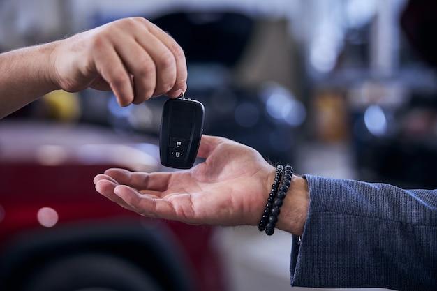 Mecânico entregando a chave do carro eletrônico moderno ao homem