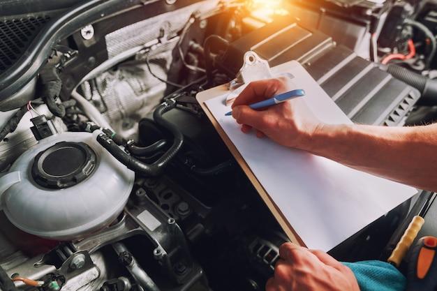 Mecânico escrevendo a lista de verificação do trabalho para a prancheta em uma oficina com um carro