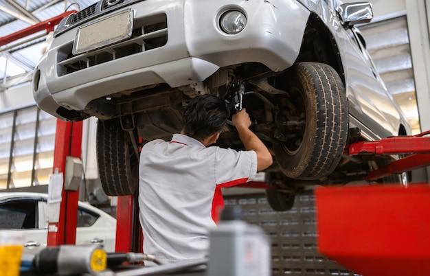 Mecânico está consertando a suspensão do carro