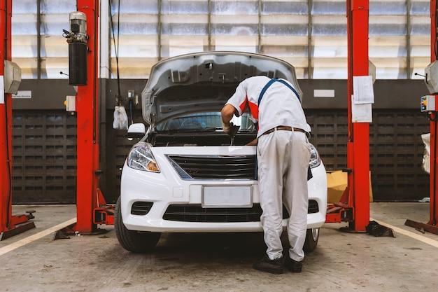 Mecânico está verificando o carro no centro de serviço de conserto de automóveis