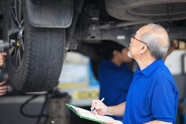 Mecânico examinando a parte inferior no serviço de automóveis, serviço de reparo de automóveis.