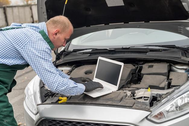 Mecânico fazendo diagnóstico de um carro com laptop