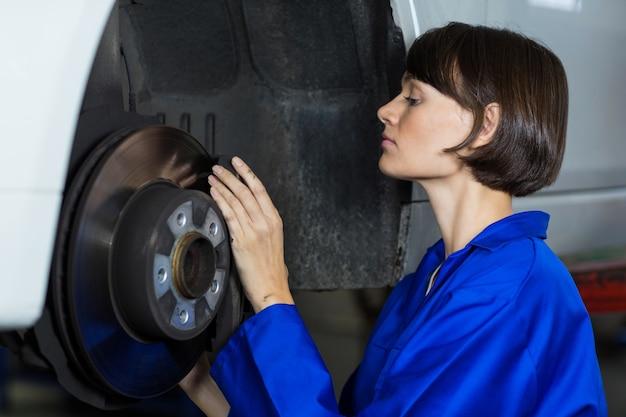 Mecânico fêmea que examina um travão de disco de roda do carro