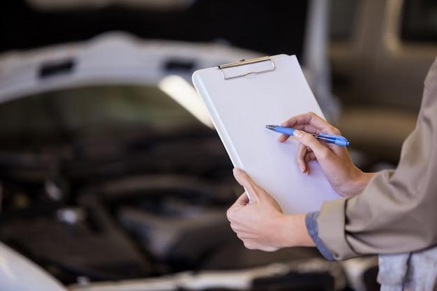 Mecânico fêmea que prepara uma lista de verificação