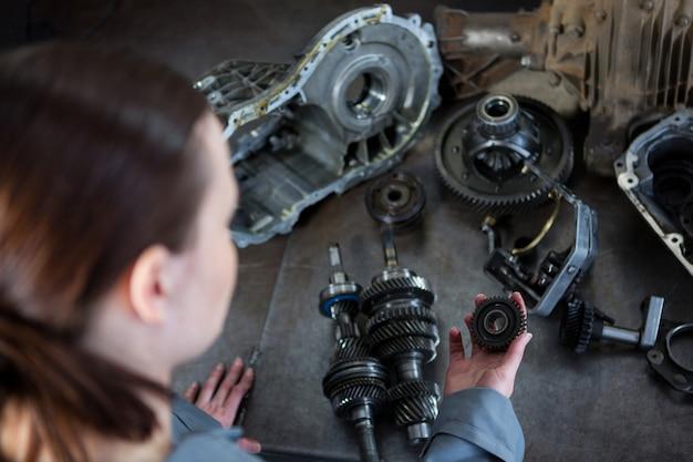Mecânico fêmea segurando peças de carro Foto gratuita