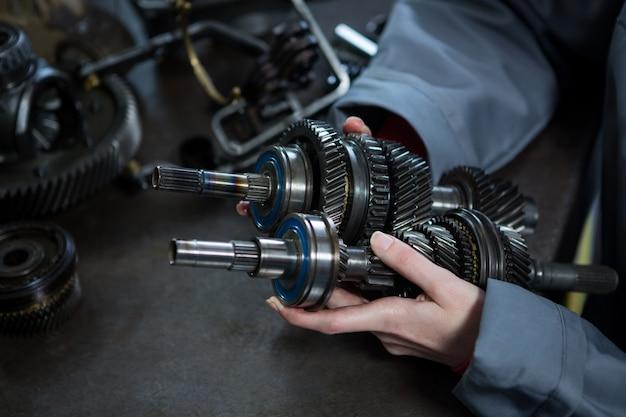 Mecânico fêmea segurando peças de carro