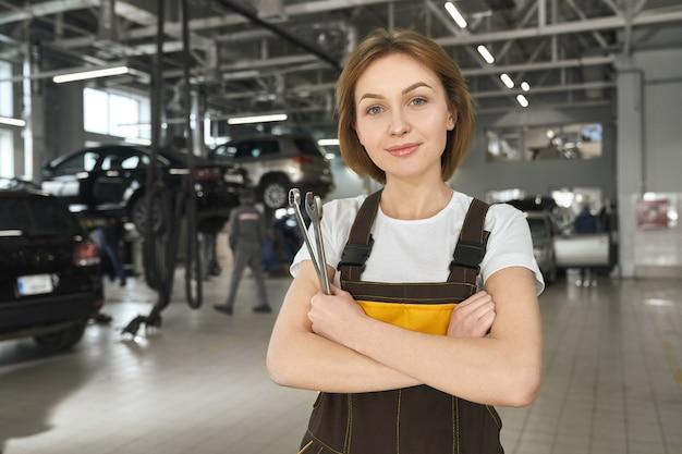 Mecânico feminino com chaves posando em serviço automático.