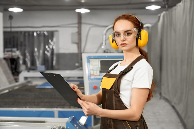 Mecânico feminino em fones de ouvido uniformes e protetores
