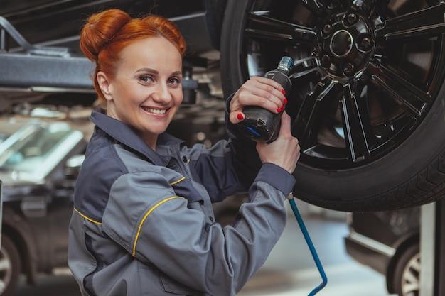 Mecânico feminino trabalhando na estação de serviço de carro