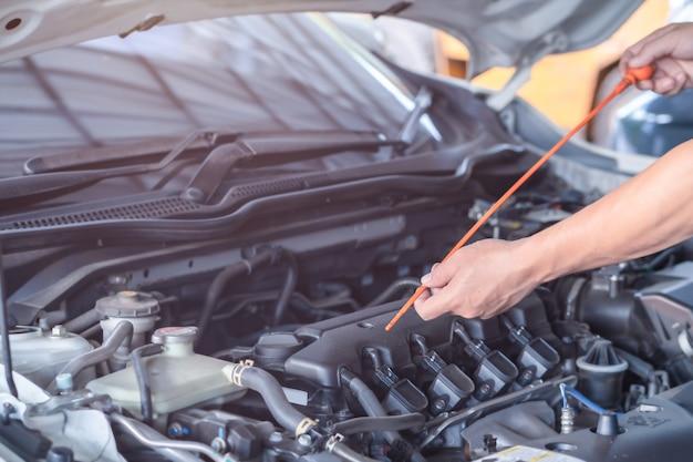 Mecânico homem verificar o nível de óleo do motor, inspeção e carro de mentenção