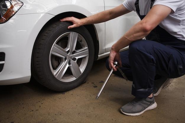 Mecânico irreconhecível examinando rodas de carro