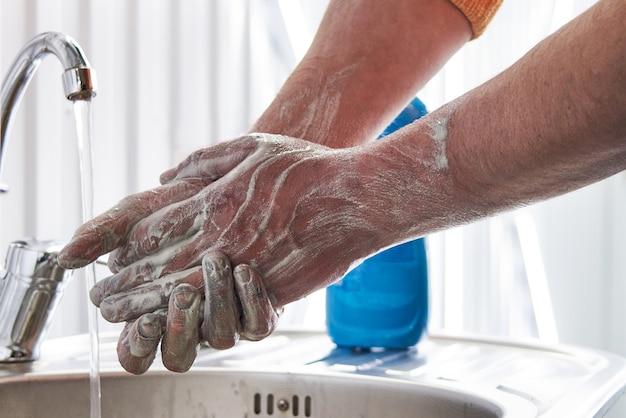 Mecânico lavando as mãos sujas com sabão depois do trabalho