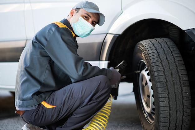 Mecânico mascarado, verificando a pressão de um pneu de van