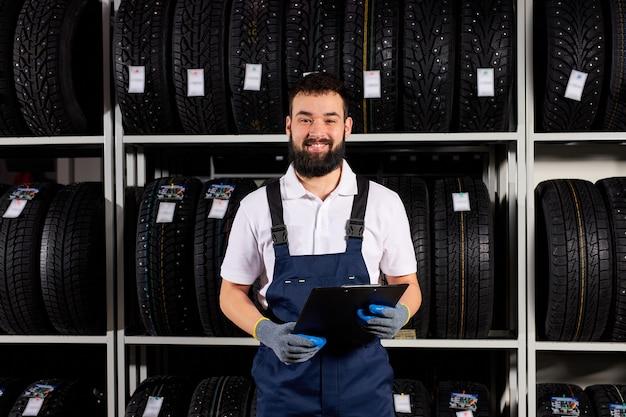 Mecânico masculino com prancheta perto de pneus no centro de serviços automotivos, olhando para a câmera e sorrindo, em uniforme azul