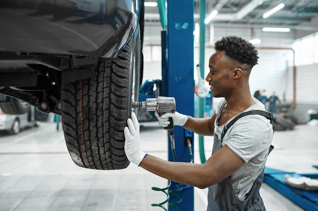 Mecânico masculino com roda de reparos de pistola pneumática, serviço de carro. garagem de conserto de veículos, homem de uniforme, interior da estação de automóveis
