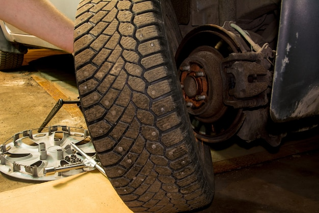 Mecânico mudando a roda do carro na garagem. homem trocando o pneu. serviço de pneus. montagem de pneu.