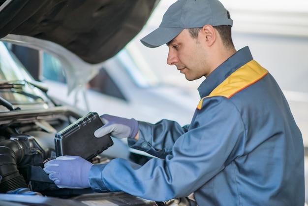 Mecânico mudando o óleo de um motor de carro, manutenção e conceito de manutenção