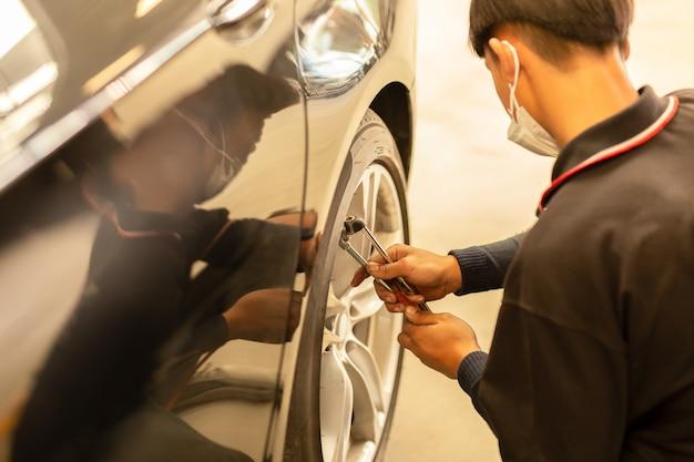 Mecânico novo que verifica a pressão de ar e que enche o ar no pneu.