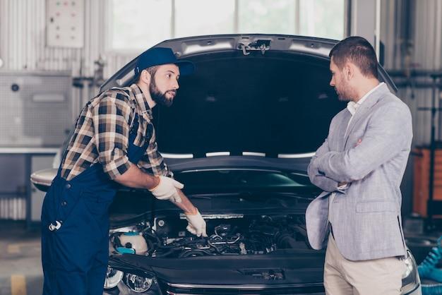 Mecânico profissional com uniforme azul de segurança, mostrando problema ao proprietário do carro