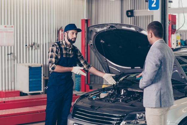 Mecânico profissional de uniforme azul conversando com o cliente