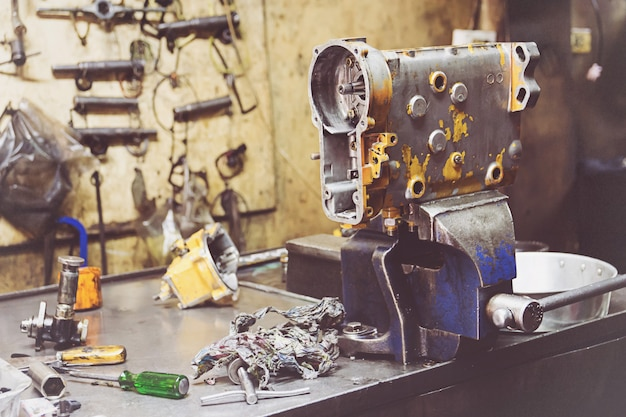 Mecânico profissional usando diferentes ferramentas para trabalhar no serviço de reparação automóvel