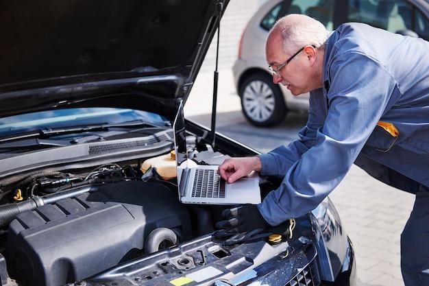 Mecânico profissional usando tecnologia contemporânea no trabalho