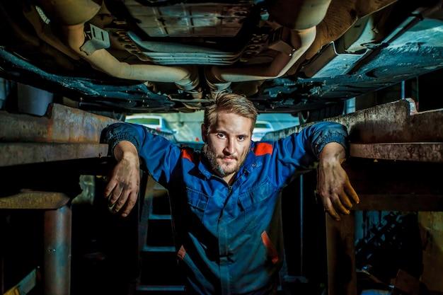 Mecânico que examina sob o carro na garagem do reparo.
